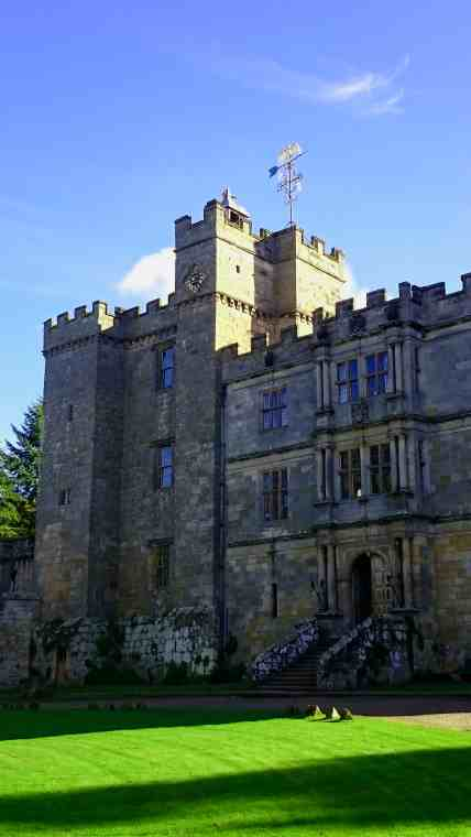 Image of front view of castle with gate and clock tower under blue sky