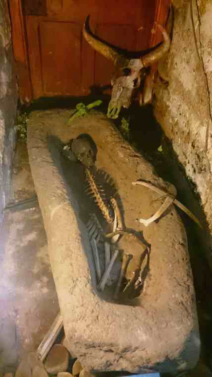 Image of genuine ancient skeleton in stone trough with animal skull behind in dark stone room