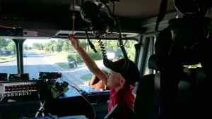 Image of girl in red T shirt and blue cap pulling cord to ring bell in cab of fire engine