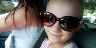 Image of girl with no hair wearing giant sunglasses in passenger seat of vehicle with woman driving in background