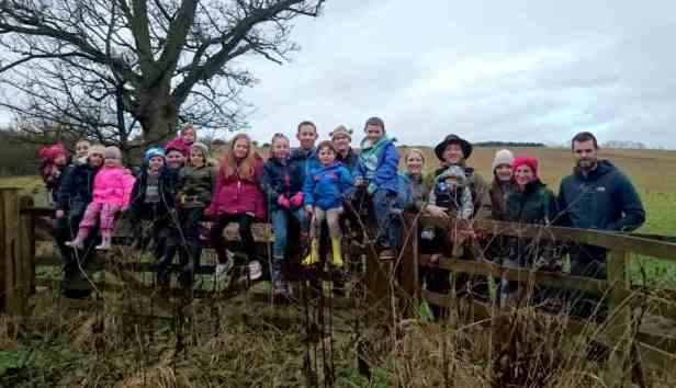 Image of group of adults and children leaning on wooden fence in field with bare tree behind and grey sky