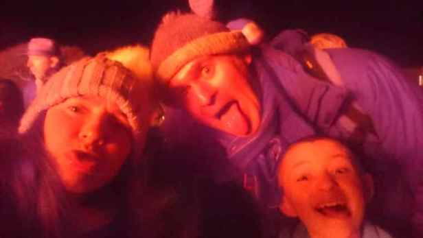 Image of mother, father and daughter wearing wooly hats and making silly faces lit up by bonfire light at night