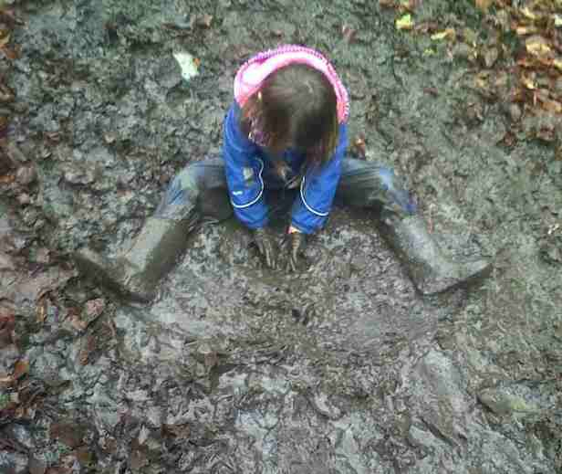 Image of toddler in blue splash suit covered in mud sat in mud on ground