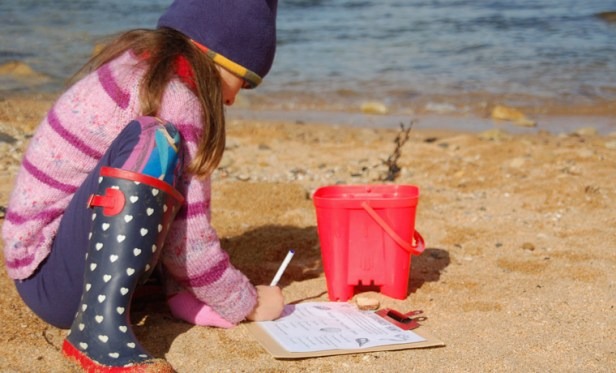 Image of girl in lilac stripe top, hat and wellies squatting on beach next to red bucket making notes on a board