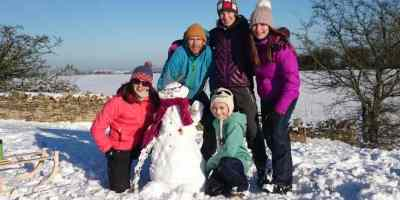 Image of family group in snow next to snowman wearing glasses with snowy landscape behind