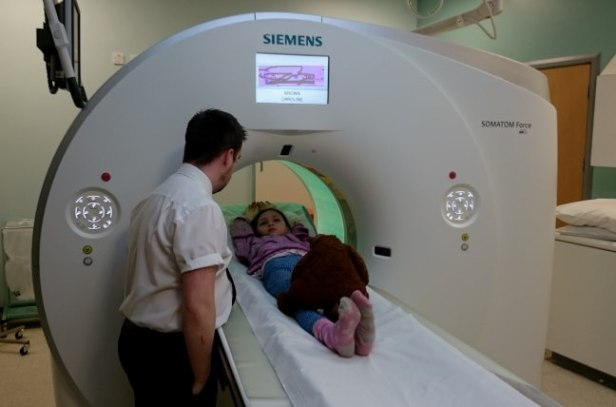 Image of girl in CT scanner with teddy on her feet and man talking to her