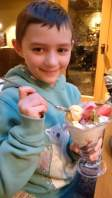 Image of girl in green Christmas jumper with Audrey Hepburn short haircut sat at dining table holding sundae glass full of icecream