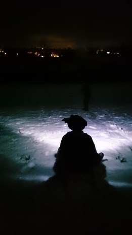 Image of silhouetted figure on sledge on snowy hill in pitch dark with street lights in distance