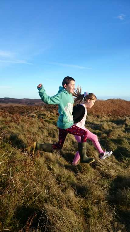 Image of two girls jumping on grassy ditch with blue sky in background