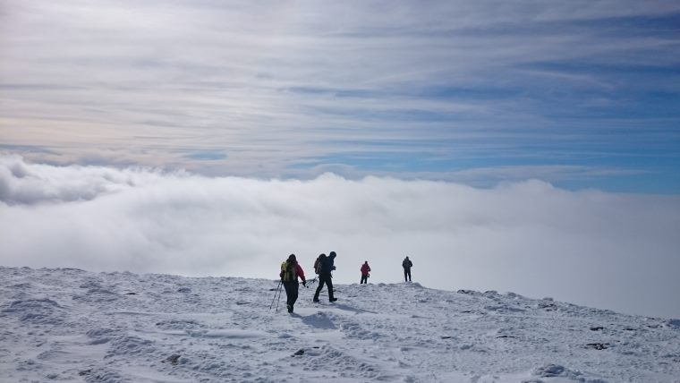 Image of 4 silhouetted people at edge of snow covered plateau on mountain peak with cloud inversion and sky behind