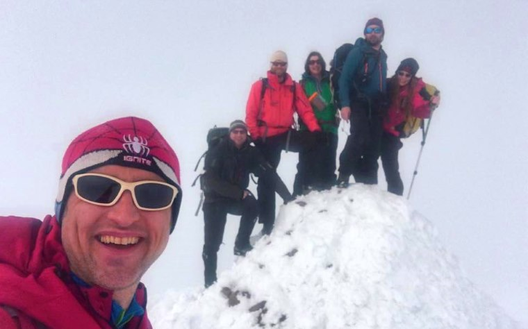 Image of 6 adults in snow gear, 5 on snow covered cairn and one in foreground taking selfie