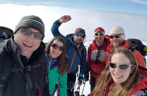 Image of 6 adults in snow gear on snow covered mountain peak with clouds and sky behind