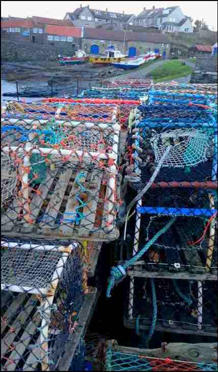 Image of coloured lobster pots with fishing boats in background of small harbour 2