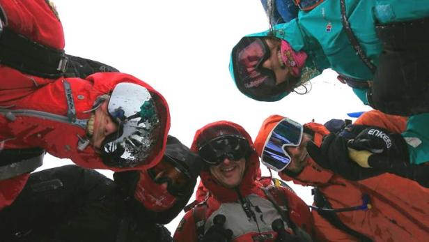 Image of five adults in winter snow gear and ski goggles looking down at camera