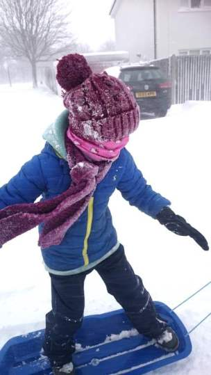 Image of girl in blue coat and burgundy hat and scarf 'snowboarding' on a sledge