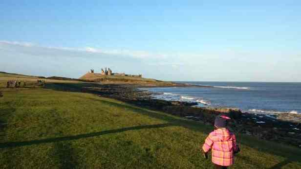 Image of girl in foreground and other people mid ground on grassy coastal path with castle and sea in background