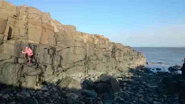 Image of girl in pink and orange coat scrambling on rocks at sea's edge