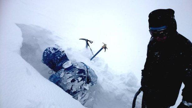Image of man in blue snow gear digging hole in mountain snow with ice axes in snow and man in black gear looking on