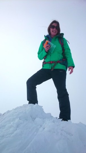 Image of woman in green snow jacket and dark trousers carrying tiny teddy bear standing on snow covered cairn on peak of mountain
