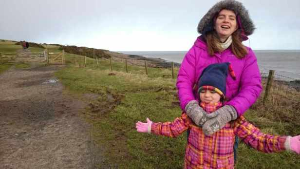 Image of woman in magenta coat and child in orange and pink coat catching snowflakes on their tongues with grey sky, coastal field and sea behind