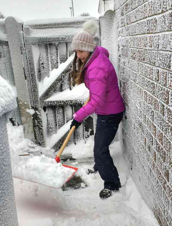 Image of woman in purple coat and waterproofs shovelling snow from a path with wooden gate behind