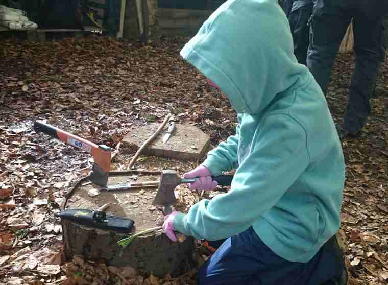 Image of child in green hoody kneeling by log in woods chopping with axe