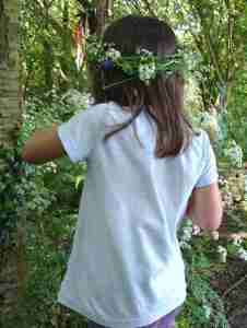 Image of child in pale blue T-shirt in woods with daisy chain in hair with back to camera