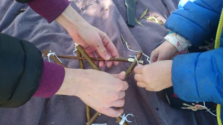Image of close up of two pairs of hands knotting string around sticks to make a star