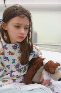 Image of girl with long hair in patterned kid's hospital gown looking very sick and sad sitting on hospital bed with bandage on hand holding a brown teddy