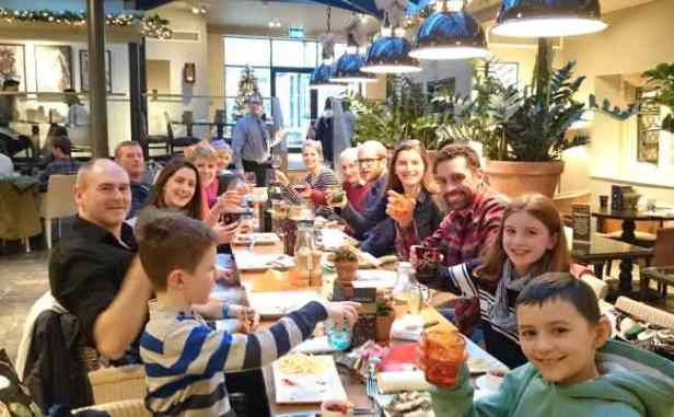 Image of group of adults and children sat around large table in restaurant at Christmas