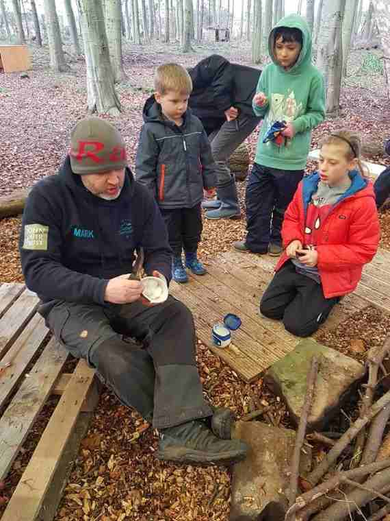 Image of man demonstrating firelighting to group of children in woods