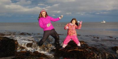 Image of woman in purple coat and waterproof trousers with girl in pink and orange waterproofs playing air guitar in waves at the sea's edge