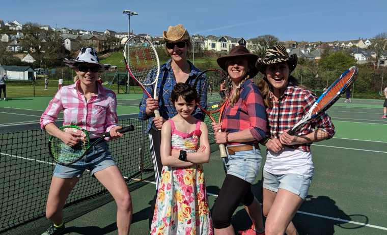 Image of 4 women in cowboy hats with tennis racqets and girl in sundress on tennis courts