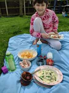 Girl in pink and red top sitting on blue picnic mat on grass with picnic food laid out