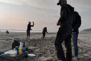 Image of silhouetted adults and child playing ball games on beach at sunset with barbecue and sea behind