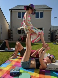 Image of woman lying on back in garden with child sitting on feet doing yoga pose