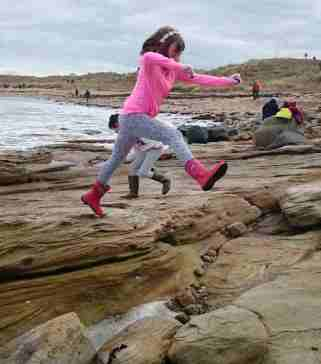 Image of girl in pink clothing jumping between rocks on beach with sea, sand and dunes in background