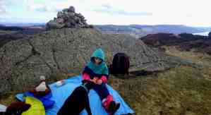 Image of girl in striped top sitting on sky blue picnic rug with black dog against cairn of stones at top of hill with view of hills, lake, sky & cloud