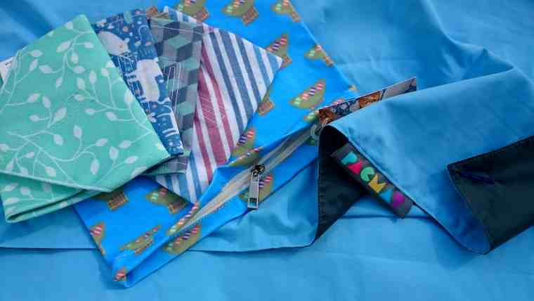 Image of sky blue blanket with turned up grey corner underneath multicoloured fabric pouches and bags