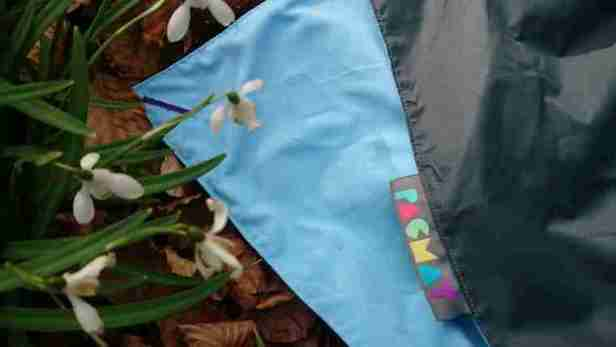 Image of snowdrops next to sky blue fabric on ground with upturned grey corner showing button hole for peg and word Pacmat on label