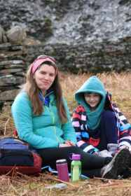 Image of woman with mouthful of food and girl laughing sitting on picnic rug on bracken and dry stone wall behind