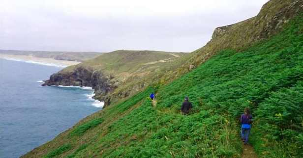 Image of 3 people walking cliff top track in deep greenery with curving sandy beach and dunes in distance and grey sky