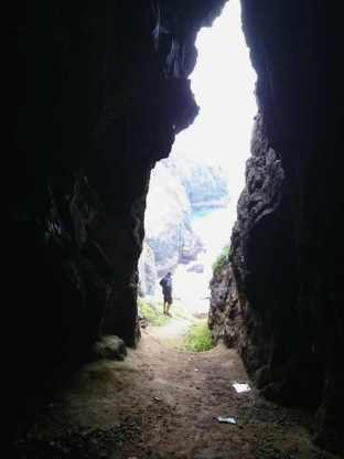 Image of dark silhouetted rock inside cave looking out through entrance to brightly lit cliffs with man standing in entrance