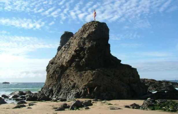 Image of figure of woman stood on top of rock island on sandy beach with sea and sky behind