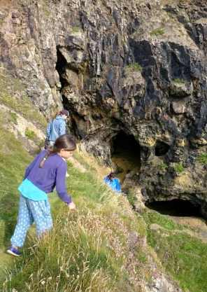 Image of girl in foreground on steep grassy cliff with adults behind climbing down track with rocky cliffs and caves behind