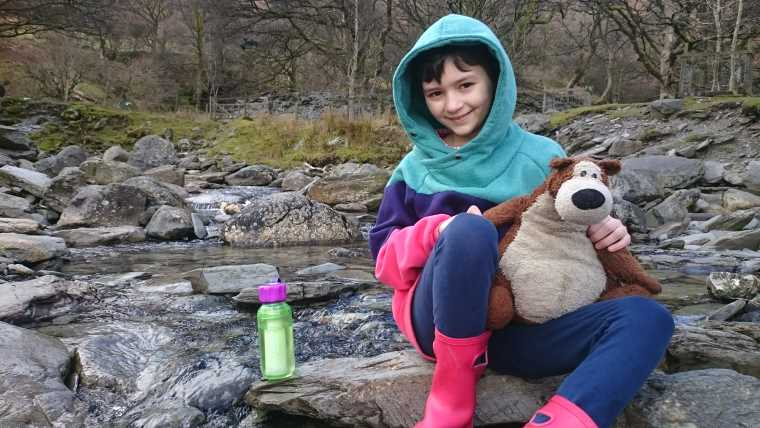 Image of girl in green and pink hoody holding brown teddy bear sat on rocks in middle of stream with green plastic drinking bottle on rock next to her