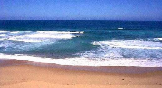 Image of beach showing white water at sea's edge with smooth stream of water between