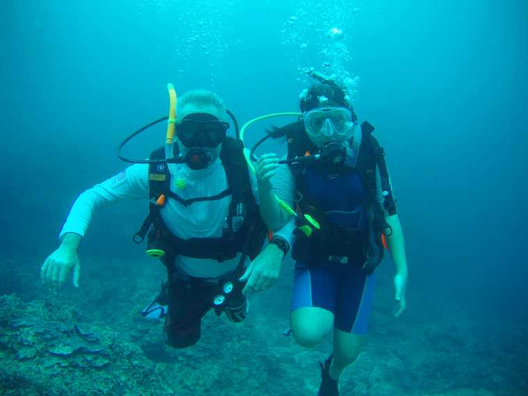 Image of two children in diving gear under water with bubbles blowing from masks