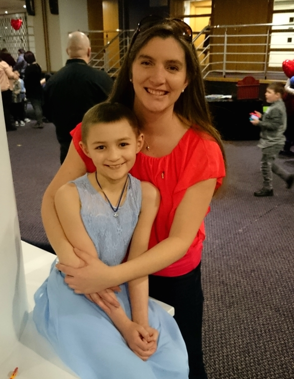 Image of woman in red top cuddling girl in blue dress with very short hair due to cancer