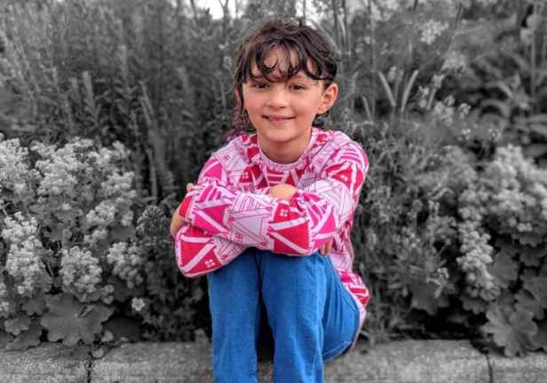 Image of dark, curly haired girl with pink pattern top and blue trousers sitting in front of flower border which is black and white